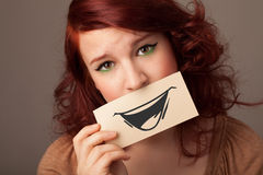 Happy cute girl holding paper with funny smiley drawing Stock Image