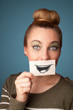 Happy cute girl holding paper with funny smiley drawing Stock Photos