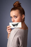 Happy cute girl holding paper with funny smiley drawing Royalty Free Stock Image