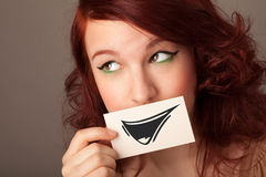 Happy cute girl holding paper with funny smiley drawing Royalty Free Stock Images