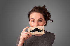 Happy cute girl holding paper with mustache drawing Royalty Free Stock Photography