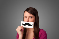 Happy cute girl holding paper with mustache drawing Stock Photography