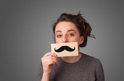 Happy cute girl holding paper with mustache drawing Stock Image