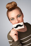 Happy cute girl holding paper with mustache drawing Royalty Free Stock Images
