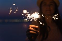 Happy cute girl holding a sparkler on beach during sunset. Celebration concept stock images