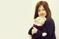 Happy cute girl hugging cute, teddy bear toy. Childhood and happiness. Happy cute small, little girl, child with brunette hair in pajamas hugging adorable, teddy royalty free stock images