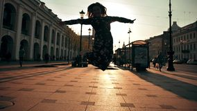 Happy cute girl jumping outdoor at city streets. stock footage