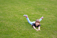 Happy cute girl lying on a lawn Royalty Free Stock Photo