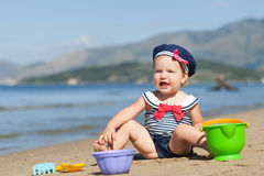 Happy cute girl in swimsuit playing with sand on beach Royalty Free Stock Photography