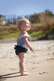Happy cute girl in swimsuit playing with sand on beach Stock Photography