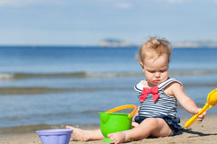Happy cute girl in swimsuit playing with sand on beach Stock Photos