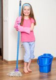 Little girl washing the floor. Happy cute girl washing the floor with a mop at home stock photos