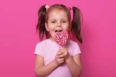 Happy cute girl wears rose t hirt, stands isolated over pink background, holds bright lollipop in hands. Cheery child with opened. Mouth tasting delicious candy royalty free stock photos