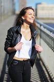 Happy cute girl in white t-shirt and black jacket goes over the bridge of the St. Petersburg channel,  laughing heartily. Happy cute girl in white t-shirt and Royalty Free Stock Photography