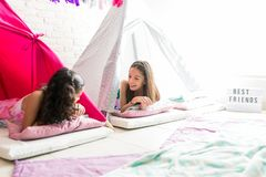 Girls Sharing Gossips While Resting In Tents During Pajama Party. Happy cute girls sharing gossips while resting in tipi tents during pajama party stock photos