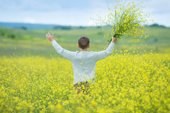Happy cute handsome little kid boy on green grass lawn with blooming yellow dandelion flowers on sunny spring or summer day. Littl Royalty Free Stock Photos