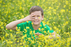 Happy cute handsome little kid boy on green grass lawn with blooming yellow dandelion flowers on sunny spring or summer day. Littl Stock Photos