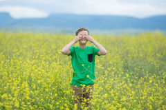 Happy cute handsome little kid boy on green grass lawn with blooming yellow dandelion flowers on sunny spring or summer day. Littl Royalty Free Stock Photo