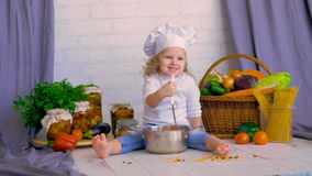 Happy cute kid in chef`s hat in the kitchen laughing, playing. stock footage