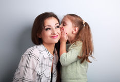 Happy cute kid girl whispering the secret to her funny grimacing Royalty Free Stock Photo