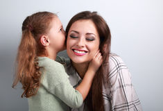 Happy cute kid girl whispering the secret to her laughing mother Stock Photography