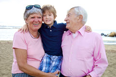 Happy cute kid hugging grandparents in vacation Royalty Free Stock Images