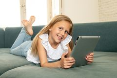 Happy cute kid learning, playing and surfing on the Internet with tablet with great interest stock photo