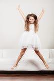 Happy cute kid little girl jumping for joy. Stock Photos