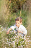 Happy cute kid picking flowers in a field Royalty Free Stock Photo