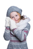 Happy cute kid posing in the studio isolated on white background. Wearing winter clothes. Knitted woolen sweater, scarf, hat and m Royalty Free Stock Images