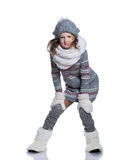 Happy cute kid posing in the studio isolated on white background. Wearing winter clothes. Knitted woolen sweater, scarf, hat Royalty Free Stock Images