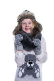 Happy cute kid posing in the studio. Wearing winter clothes. Knitted woolen sweater and mittens. Ear flaps fur cap. Royalty Free Stock Images