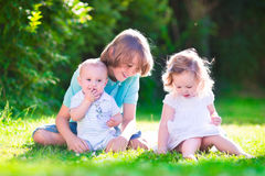 Happy cute kids in the garden. Three happy kids, brothers and sister, laughing teenager boy, little baby and a funny curly girl playing together with flowers in royalty free stock image