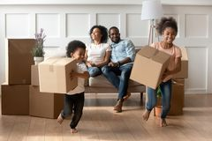 Happy little african kids holding boxes play on moving day. Happy cute little african kids holding boxes run play in living room while parents relax on sofa on stock photography