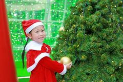 Happy cute little Asian child girl in Santa costume near Christmas tree and background. Christmas winter holiday concept royalty free stock images