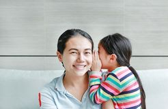 Happy cute little Asian child girl whispering a secret to her young mothers ear at home. Family and relationships concept stock image