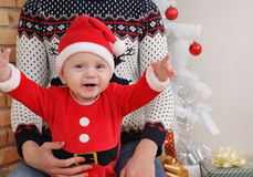 Happy cute little baby boy in Santa suit sitting on mother's kne Stock Image