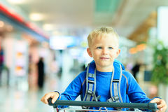 Happy cute little boy at airport riding on luggage Royalty Free Stock Images