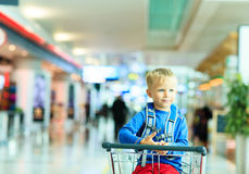 Happy cute little boy at airport riding on luggage Stock Images