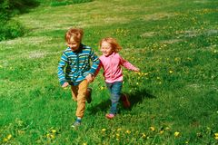 Happy little boy and girl run in spring nature Royalty Free Stock Image