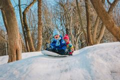 Happy cute little boy and girl slide in winter snow. Seasonal activities stock images