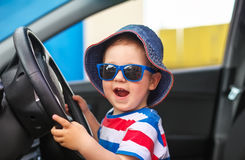 Happy cute little boy with glasses sitting in the car Royalty Free Stock Photography