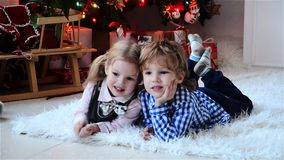 Happy Cute little boy and his beautiful sister at Christmas, children laughing while lying on the floor near a Christmas stock video footage