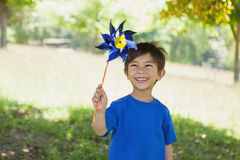 Happy cute little boy holding pinwheel at park Stock Photography