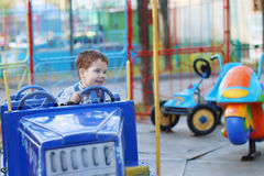 Happy cute little boy rides on car of carousel Royalty Free Stock Images