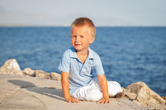 Happy cute little boy sitting on sand at beach Stock Photo