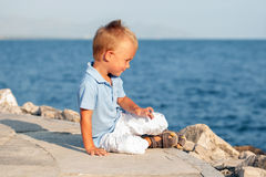 Happy cute little boy sitting on sand at beach Royalty Free Stock Image