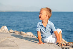 Happy cute little boy sitting on sand at beach Stock Photography