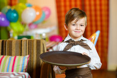 Happy cute little boy smiling waiter holding a Stock Photography