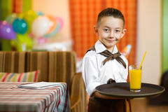 Happy cute little boy smiling waiter holding a Stock Photos